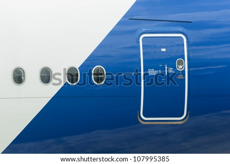 emergency exit and windows on the fuselage of a passenger aircraft - stock photo