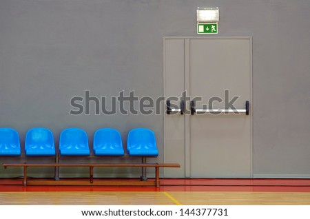 Emergency exit door next to a row of blue sits in a sports pavilion - stock photo