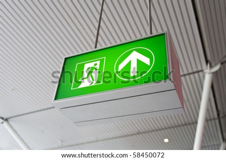 Emergency exit sign glowing green - stock photo