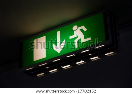 Emergency exit sign glowing green in the dark - stock photo