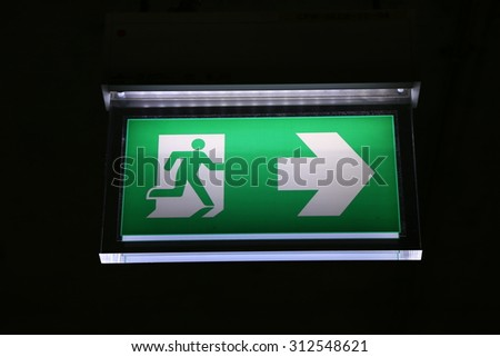 Emergency exit sign glowing in the dark - stock photo