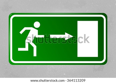 Emergency exit sign hanging on a concrete wall - stock photo