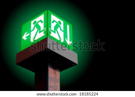 Emergency exit sign in a building glowing green light on black background - stock photo