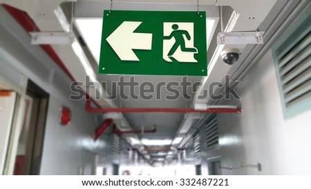 Emergency exit sign in hallway of apartment - stock photo