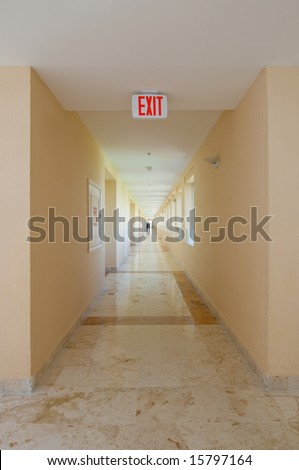 Emergency exit sign in hotel hallway - stock photo