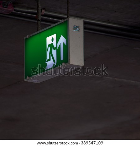 Emergency exit sign under the ceiling indoor at dark area. - stock photo