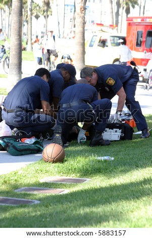 Emergency in Vencie Beach California. An unknown unidentifiable person suffers an apparent Heart Attack while playing basket ball. - stock photo