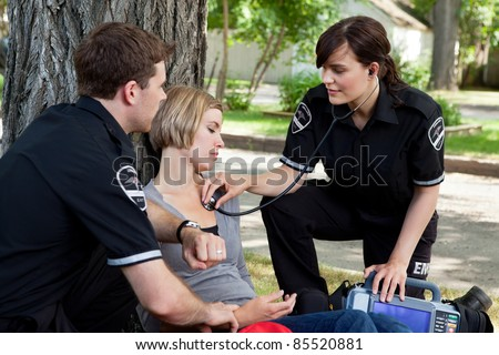 Emergency medical professionals assessing an injured patient - stock photo
