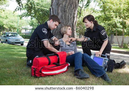 Emergency medical professionals assessing an injured patient on the street - stock photo