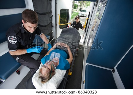Emergency medical professionals  caring for senior patient - stock photo