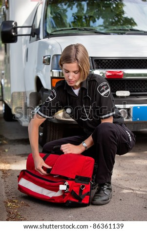 Emergency medical services professioanl opening a portable oxygen unit near ambulance - stock photo