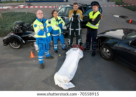 Emergency Medical Services team posing over an injured driver at the scene of a car crash - stock photo