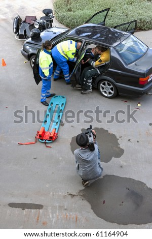 Emergency medical services team rescuing a wounded woman with neck injury from her damaged car after an accident, with the press present at a distance - stock photo