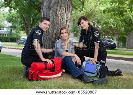 Emergency medical team treating a patient on the street - stock photo