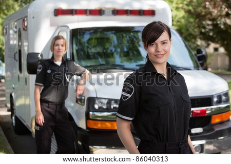 Emergency medical workers standing with ambulance - stock photo