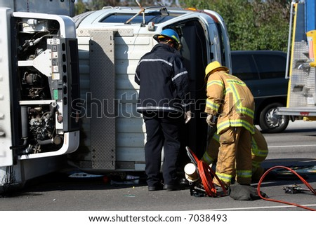 Emergency personnel at the scene of a turned truck - stock photo