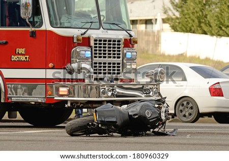 Emergency responders at the scene of a motorcycle vs car at a busy intersection that left the rider with serious injuries. - stock photo