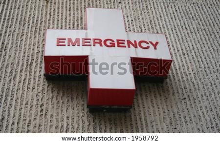 Emergency room symbol red writing on white cross - stock photo