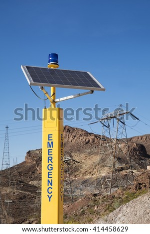 Emergency solar cell pole with high voltage electricity pole on the mountain in background - stock photo