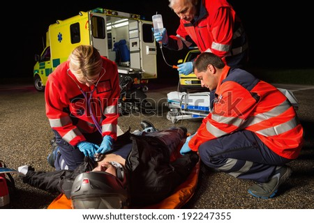 Emergency team helping injured motorbike man driver at night - stock photo