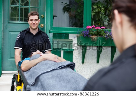 Emergency team pushing a woman out of a residential house - stock photo