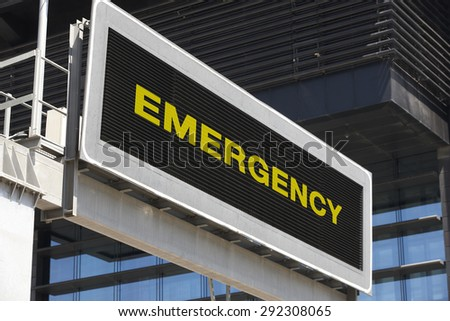 Emergency traffic signpost in the city with building facade background. Horizontal