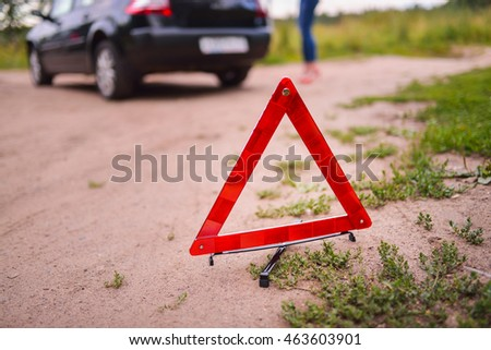 Emergency triangle stop sign on the road. Stopped car a in the background