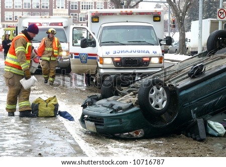 Emergency workers respond to the scene of a single vehicle rollover. - stock photo