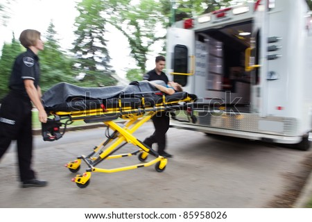 Emergency workers rushing senior woman into an ambulance - stock photo