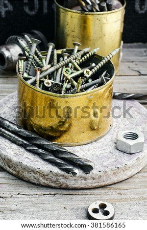 Emery wheel and a set of drill bits and screws on wooden background - stock photo