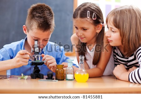 Eminent elementary school boy looking into microscope while girls are watching
