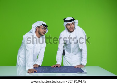 Emirati businessmen with blueprint at office - stock photo