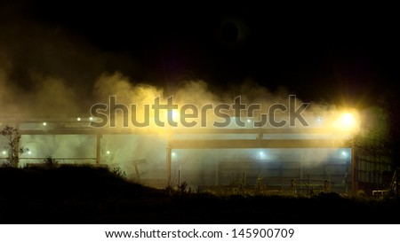 Emissions from a factory at night with light diffused through smoke haze - stock photo