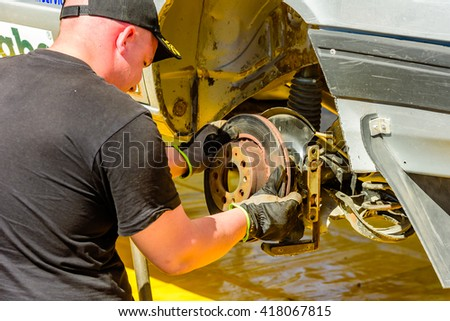 Emmaboda, Sweden - May 7, 2016: 41st South Swedish Rally in service depot. Mechanic mounting brakes on the rear wheel of a car.