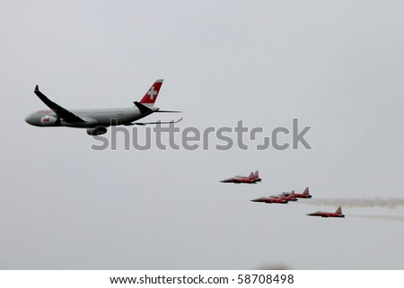 "EMMEN - JULY 24: Swissair showcases it?s latest plane an Airbus  A330-300 guarded by Tiger Jets of Patrouille Suisse at the Airshow ""100 years Swiss aviation"" July 24, 2010 in Emmen, Switzerland."