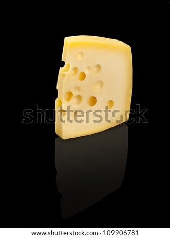 Emmental cheese with holes, isolated on black background. - stock photo