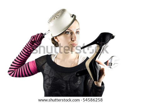 EMO girl - housekeeper with shoe, instrument and pan on the head - stock photo