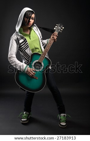 emo girl with guitar on black background - stock photo