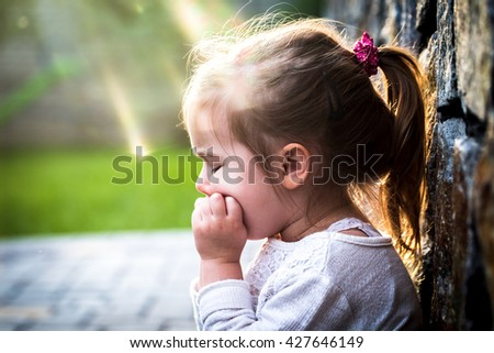 emotion girl sitting near wall in the day time, beautiful background - stock photo