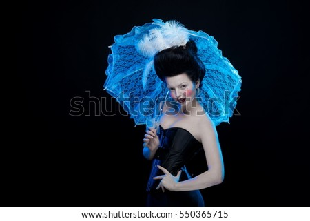 emotional actress brunette woman in an ancient medieval attire and lush hair with white feathers with a white lace umbrella in hand on a black background in the studio