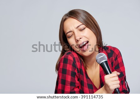 Emotional attractive teen girl singing a song with inspiration in microphone, over grey background - stock photo