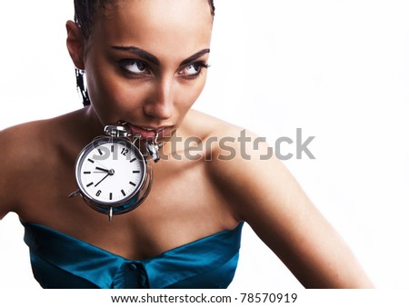 Emotional beautiful mulatto girl holds an alarm clock in a teeth. Studio photo - isolated on white. - stock photo