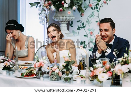 Emotional beautiful newlywed couple smiling at wedding reception - stock photo
