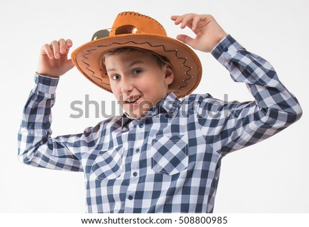 Emotional blond boy in a plaid shirt, sunglasses and a cowboy hat on a white background