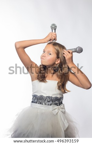 Emotional blonde girl in a white dress singing into a microphone on a white background