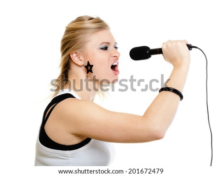 emotional blonde girl singer performer singing to microphone isolated on white. young pretty rockstar holding wireless mike