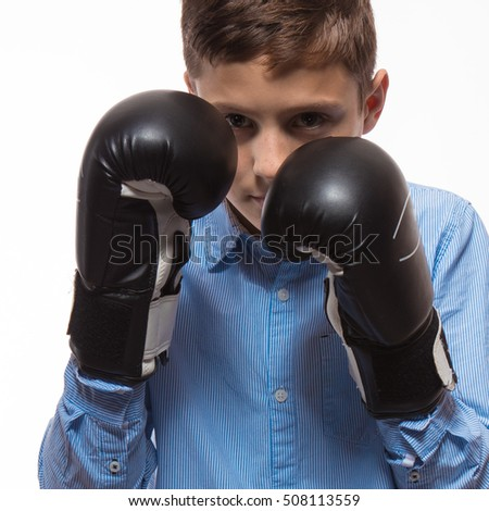 Emotional boy brunette in a blue shirt with boxing gloves in hands on a white background