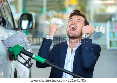 Emotional businessman counting money with gasoline refueling car at fuel station - stock photo