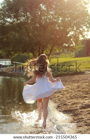 Emotional cheerful little girl in a white dress runs along the lake shore in summer - stock photo