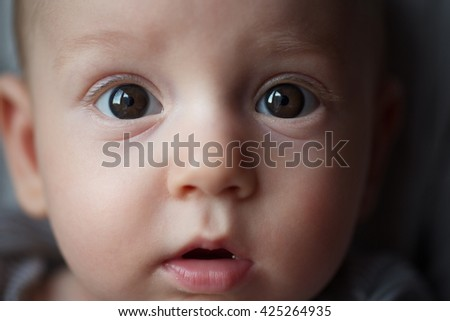 emotional close-up portrait of little baby boy with curious funny face selective focus